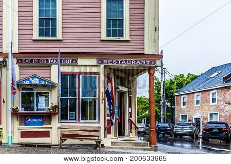 Castine USA - June 9 2017: Empty small village in Maine during rain with brick restaurant building and take out window