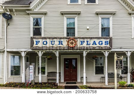 Castine USA - June 9 2017: Empty small village in Maine during rain with Four Flags gift shop sign with ship steering helm