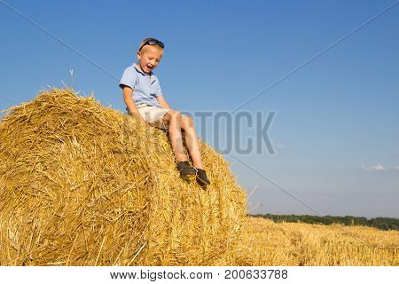 Laughing boy in the field with bundles of hay