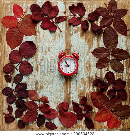 Flat lay frame of autumn crimson leaves with red alarm clock on a blue wooden background. Selective focus.