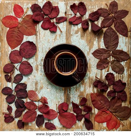 Flat lay frame in the form of a heart of autumn crimson leaves on a blue wooden background with a cup of coffee. Selective focus.