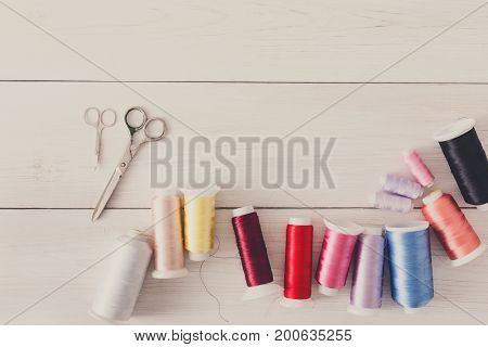 Colorful thread spools and scissors on wooden table flat lay background. Sewing string spools, copy space for text. Art, handicraft concept