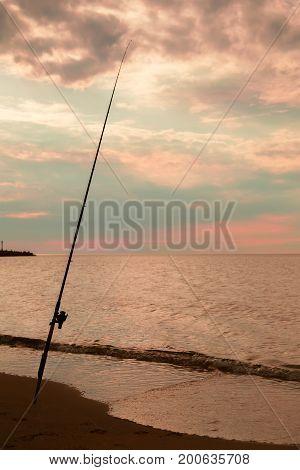 rod on the sea coast night fishing at golden sunset