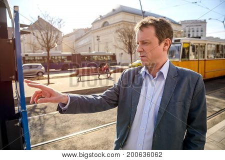 A middle age businessman checking the timetable at a tram station