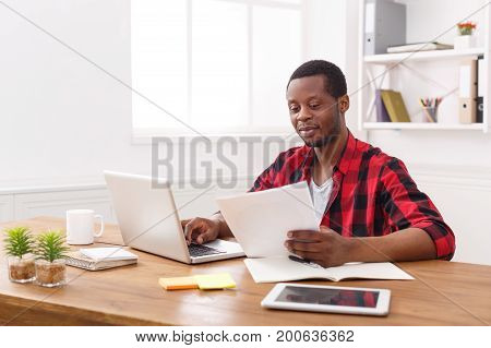 Happy black businessman in office, work with laptop and documents with pleasure