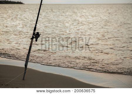 rod on the sea coast evening fishing at golden sunset
