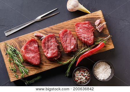 Raw filet mignon steaks with herbs and spices. Modern restaurant cuisine still life with fresh beef, salt, rosemary, garlic, chilli, meat fork on wooden board at black background, copy space, top view
