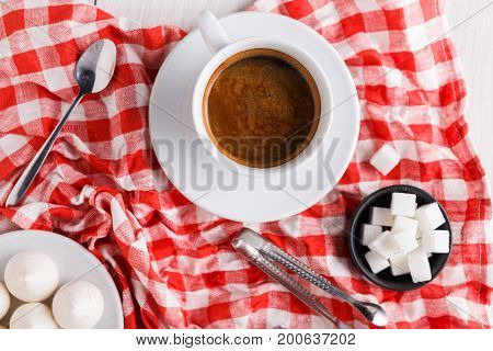 Coffee time background. Treats and cup of coffee on white and red checkered cloth. Lump sugar and meringues on white wood, top view, copy space