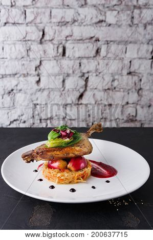 Exclusive restaurant meals. Duck confit with braised cabbage, baked apple and cranberry sauce served on snow white plate on black table at brick background with copy space