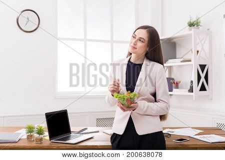 Young business woman eating salad at office, having healthy lunch at workplace