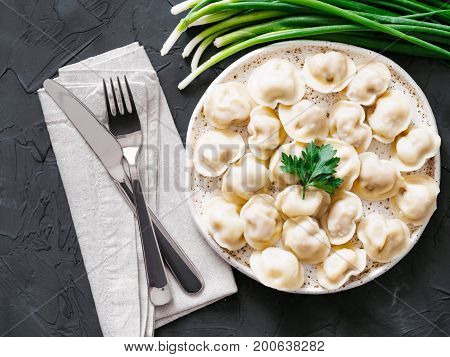 Traditional russian pelmeni, ravioli, dumplings with meat on black concrete background. Top view or flat lay. Russian food and russian kitchen concept.
