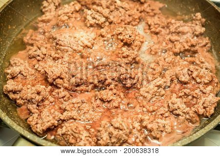 Closeup of minced meat being cooked on skillet
