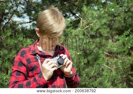 Teen is holding, study  an old and vintage photo-camera in red checkered shirt. Outdoors.