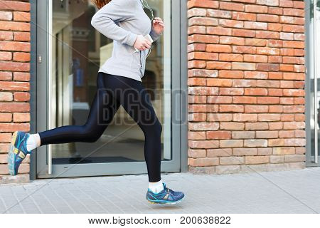 Unrecognizable woman jogging in city near brick building with mirror windows, copy space, side view