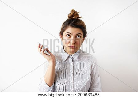 Picture of annoyed young secretary with hair knot dressed in blouse rolling her eyes while having annoying phone conversation holding mobile phone away from her ear not listening to interlocutor