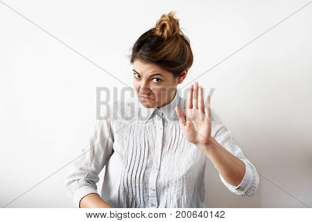 Negative human facial expressions emotions feelings attitude and reaction. Indoor portrait of displeased dissatisfied young female office worker or businesswoman gesturing showing stop sign