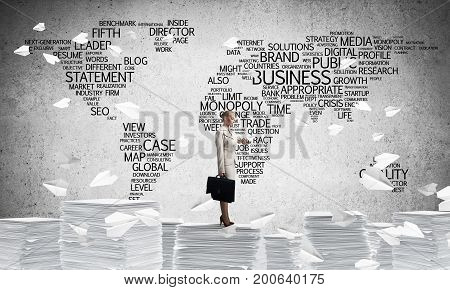 Business woman in suit standing among flying paper planes with business-related terms in form of world map on background. Mixed media.