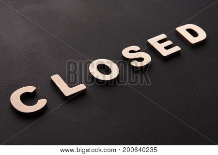 Word Closed on black background. End of working day, bankruptcy concept