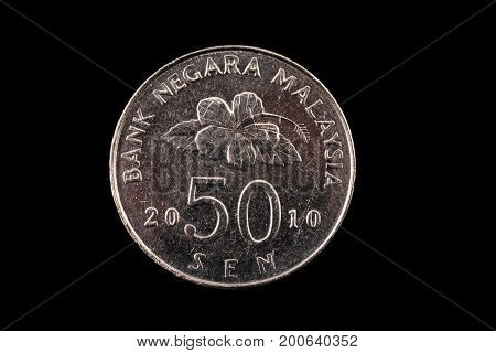 An extreme close up of an Malaysian 50 sen coin on a solid black background