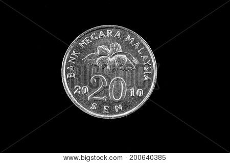 An extreme close up of an Malaysian twenty sen coin on a solid black background