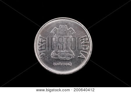 An extreme close up of an Indian two rupee coin on a solid black background