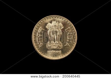 An extreme close up of an Indian five rupee coin on a solid black background