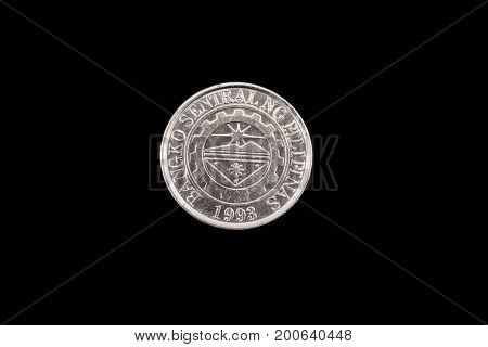 An extreme close up of an Filipino one piso coin on a solid black background