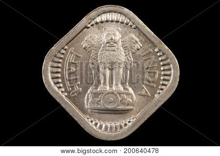 A close up of an old indian square coin on a black background