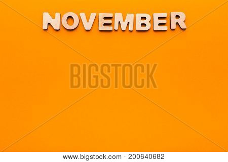 Word November made of wooden letters on orange background. Month planning, timetable concept
