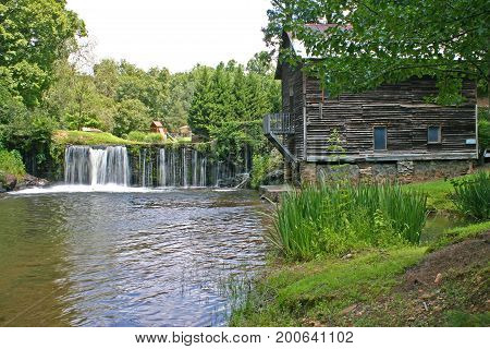 water pours over a dam next to an old gristmill