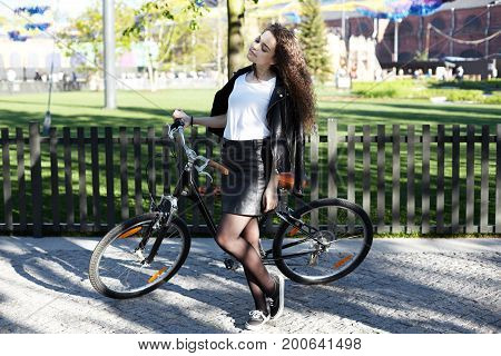 Carefree fashionable student girl with long bushy hair relaxing outdoors standing on cobblestone paved road with retro bicycle enjoying warm spring day wearing stylish clothing. Active lifestyle