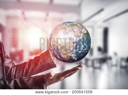 Cropped image of business woman in suit holding Earth globe in hands with sunlight and office view on background. Elements of this image are furnished by NASA.