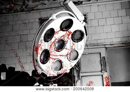 Close up view to surgical lamp sprinkled with blood in creepy abandoned hospital. Horror about maniac concept