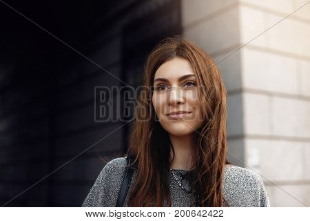 Portrait of gorgeous brunette young Caucasian female posing outdoors having happy expression on her face enjoying good day in urban surroundings. People leisure modern lifesyle and relaxation