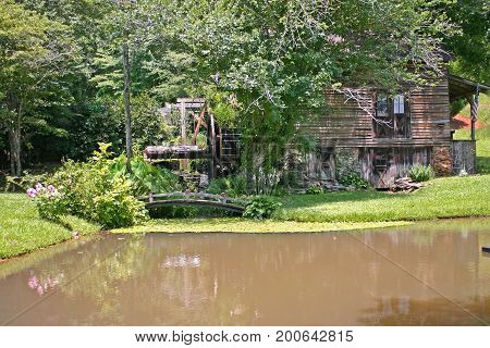 an old gristmill behind a muddy pond