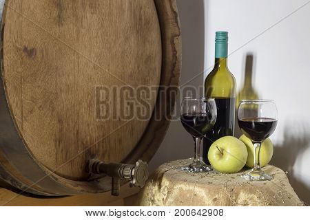 Still Life with a keg, bottle, apple and glasses of wine close-up