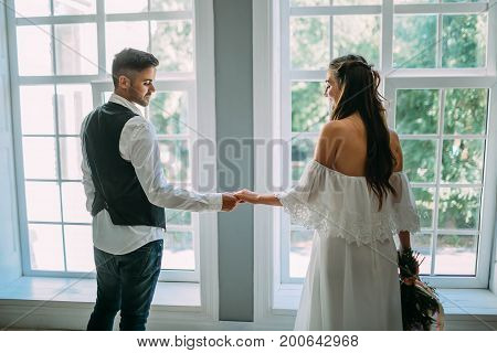 Charming Bride And Groom Are Holding Hands On Panoramic Window Background. Back View. Wedding Indoor