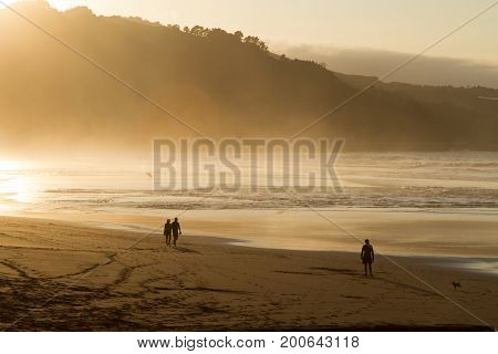A group of people trek along the wet shore at dusk. Spain.