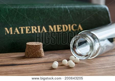 A bottle of homeopathic globules with a homeopathic materia medica in the background