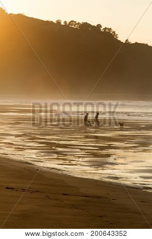 Two surfers sit on the shore of the ocean watching the sunset. Spain.