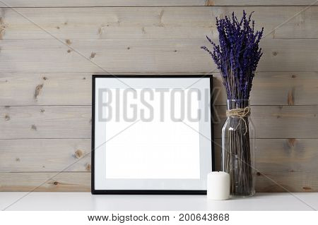 Close up picture of foursquare space photo frame with copy space white paraffin candle and glass vase with dried lavender flowers in it. Ideas for interior decor decoration and design concept