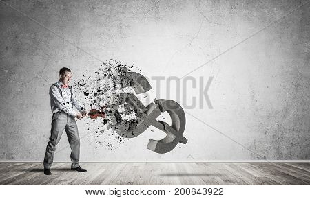 Young furious businessman in empty room crashing with violin stone dollar symbol
