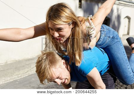 Lifestyle picture of unhappy frustrated bearded blonde guy carrying his bossy posessive girlfriend giving her piggy back ride outdoors. Happy beautiful woman walking all over her pushover boyfriend