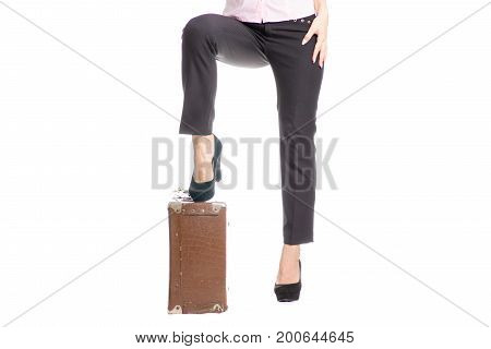Legs of a young girl in tuffle bags old suitcase on a white background isolation