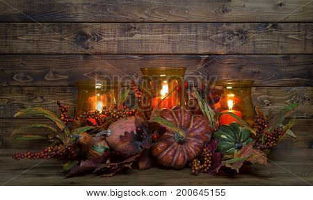 Autumn candle decoration on a rustic wood background