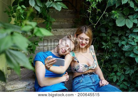 Cheerful young couple dressed in stylish summer clothes relaxing on concrete stairs using mobile phone smiling broadly taking selfie or video via social networks to share moment with friends