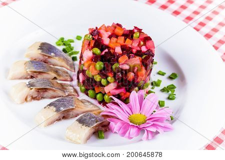 Salad vinaigrette and salted herring on a white plate