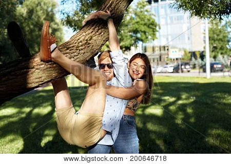 Picture of happy emotional playful young couple having fun outdoors in park. Beautiful girl laughing holding hands around back of man who is hanging on tree. Youth love relationships and happiness