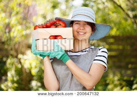 Portrait of woman in hat with tomato box in garden