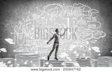 Man in casual wear keeping hand with book up while standing among flying paper planes with business-analytical information on background. Mixed media.